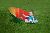 Little boy with a big rainbow umbrella — Stock Photo