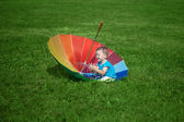 Little boy with a big rainbow umbrella — Stock Photo