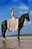 Woman on a horse by the sea — Foto de Stock
