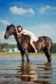 Woman on a horse by the sea — Stock Photo