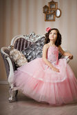 Child on a chair in a nice dress — Foto de Stock
