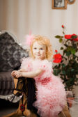 Ñhild in a pink dress on a toy horse — Stock Photo
