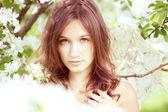 Vacker flicka i den grönskande vår trädgården — Stockfoto