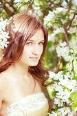 Beautiful girl in the lush spring garden — Stock Photo