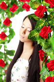 Beautiful girl with bright make-up among the roses — Stock Photo