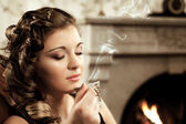 Girl drinking coffee by the fireplace — Stock Photo