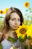 Woman with blue eyes with sunflowers — Stock Photo