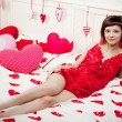 Woman in bed with hearts - Stock Photo