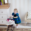 Cute girl with toy pram — Stock Photo #11934350