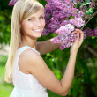 Smiling beautiful woman with violet flowers — Stock Photo