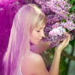 Foto Stock: Smiling beautiful woman with violet flowers