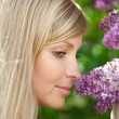 Smiling beautiful woman with violet flowers — Stock Photo #11937550