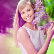 Smiling beautiful woman with violet flowers — Stock Photo #11937579