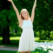 Young smiling woman with arms raised outdoors — Stock Photo #11937602