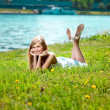 Foto Stock: Beautiful smiling woman lying on the grass