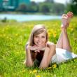 Beautiful smiling woman lying on the grass — Stock Photo