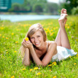 Beautiful smiling woman lying on the grass — Stock Photo #11937694