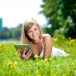 Beautiful smiling woman with tablet pc, outdoors — Stock Photo #11937839