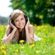 Beautiful smiling woman Woman listening to music on headphones o — Stock Photo
