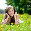 Beautiful smiling woman Woman listening to music on headphones o — Stock Photo #11938212