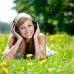 Beautiful smiling woman Woman listening to music on headphones o — Stock Photo #11938212