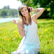 Smiling woman Woman listening to music on headphones outdoors — Stock Photo