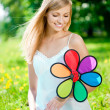 Smiling woman with a rainbow flower outdoors — Stock Photo #11938297