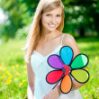 Photo: Smiling woman with a rainbow flower outdoors