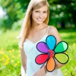 图库照片: Smiling woman with a rainbow flower outdoors