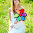 Smiling woman with a rainbow flower outdoors — Stock Photo