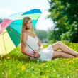 Smiling woman with a rainbow umbrella outdoors — Stock Photo #11938412
