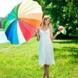 Beautiful smiling woman with two rainbow umbrellas, outdoors — Stock fotografie