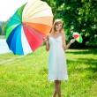 krásná usměvavá žena s dvěma duhové deštníky, venku — Stock fotografie