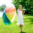 Beautiful smiling woman with two rainbow umbrellas, outdoors — Stockfoto