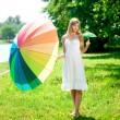 bela mulher sorridente com dois guarda-chuvas de arco-íris, ao ar livre — Foto Stock