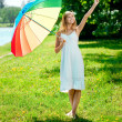 Smiling woman chooses big or small rainbow umbrella outdoors — Stock Photo #11938568