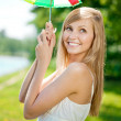 Smiling woman with a rainbow umbrella outdoors — Stock Photo
