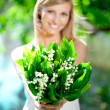Young woman smiling and give a bouquet of flowers — Stock Photo