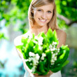 Young woman smiling and give a bouquet of flowers - Stock Photo