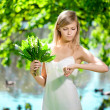 Young artistic woman with flowers outdoors — Stock Photo