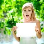 belle jeune femme souriante avec vide affiche à l'extérieur — Photo