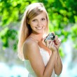 Beautiful smiling woman with a camera, outdoors — ストック写真