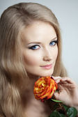 Beautiful woman with a rose — Stock Photo