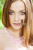 Woman with a dragonfly on her face — Stock Photo
