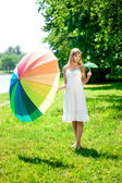 Beautiful smiling woman with two rainbow umbrellas, outdoors — Stock Photo
