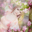 Beautiful woman and flowering tree — Stock Photo