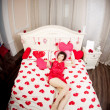 Woman in bed with hearts — Stockfoto