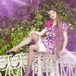 donna con una treccia di capelli in un parco fiorito — Foto Stock