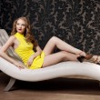 Luxury woman in a short yellow dress — Stockfoto