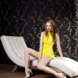 Luxury woman in a short yellow dress — Stock Photo
